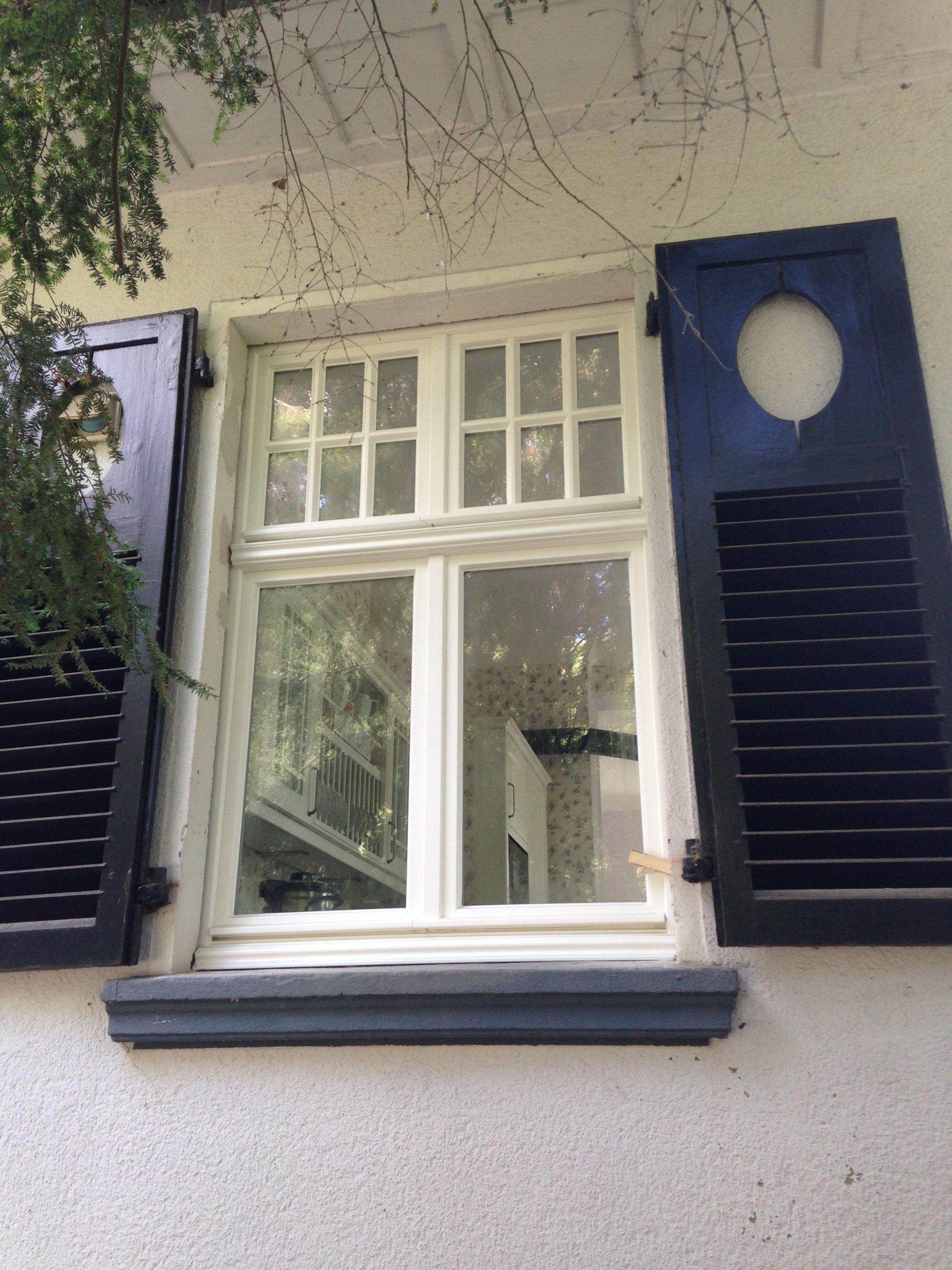 weißes Fenster mit blauen Laden.